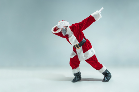 Funny serious guy with christmas hat dancing at studio. New Year Holiday. Christmas, x-mas, winter, gifts concept. Man wearing Santa Claus costume on gray. Copy space. Winter sales.