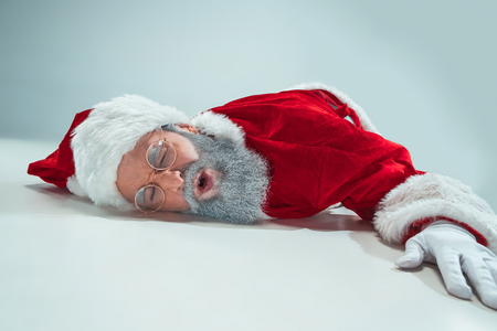 The tired Santa Claus lying on floor on white studio background. Man wearing Santa Claus costume on gray. Copy space. Winter sales. Stock Photo