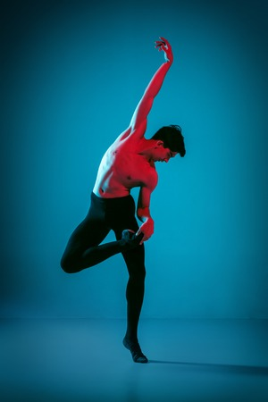 The male athletic ballet dancer performing dance on vivid blue background. Studio shot. Modern ballet, contemporary concept. Fit young man. Caucasian model