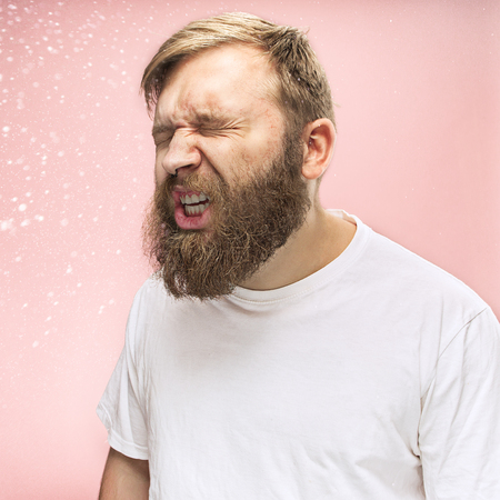Young funny handsome man with beard and mustache sneezing with spray and small drops, studio portrait on pink background. Comic, caricature, humor. illness, infection, ache. Health concept Banque d'images - 108360968