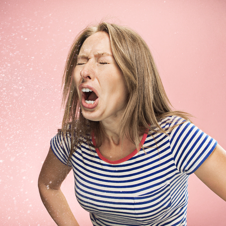 Young funny woman sneezing with spray and small drops, studio portrait on pink background. Comic, caricature, humor. illness, infection, ache. Health concept
