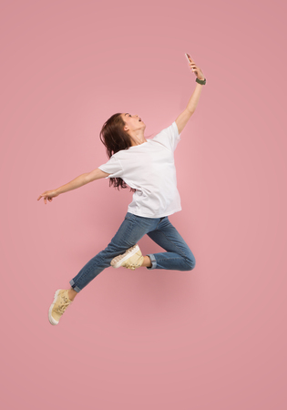 Always on mobile. Full length of pretty young woman taking phone and making selfie while jumping against pink studio background. Mobile, motion, movement, business concepts Фото со стока