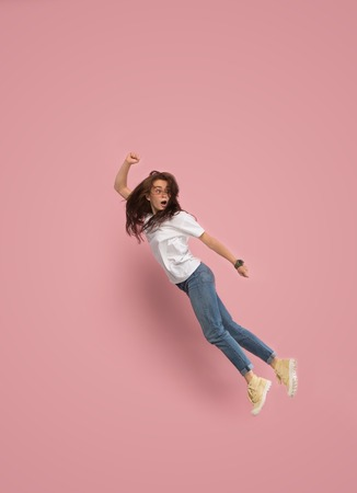 Freedom in moving. Mid-air shot of pretty frightened running away young woman jumping against pink studio background. Runnin girl in motion or movement. Human emotions and facial expressions concept
