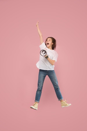 Beautiful young woman jumping with megaphone isolated over pink background. Runnin girl in motion or movement. Human emotions and facial expressions concept