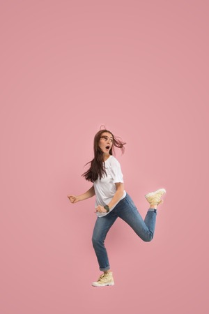 Freedom in moving. Mid-air shot of pretty frightened running away young woman jumping against pink studio background. Runnin girl in motion or movement. Human emotions and facial expressions concept 스톡 콘텐츠 - 108574490