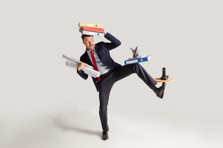 Young businessman in a suit juggling with office supplies in his office, isolated on white background. Conceptual collage with phone, folders. The business, office, work concept.