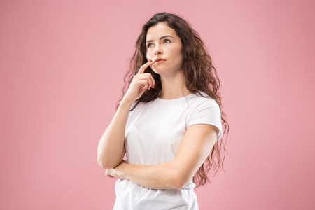 Remember all. Let me think. Doubt concept. Doubtful, thoughtful woman remembering something. Young emotional woman. Human emotions, facial expression concept. Studio. Isolated on trendy pink. Front