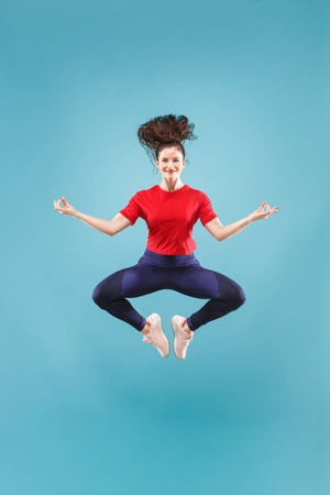 I am happy. Mid-air shot of pretty smiling young woman jumping and gesturing against pink studio background. Runnin girl in motion or movement. Human emotions and facial expressions concept