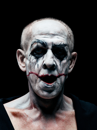 Bloody Halloween theme: The crazy smiling maniak face on dark studio background