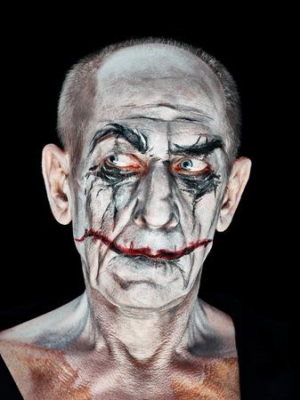 Bloody Halloween theme: The crazy maniak face on dark studio background Stock Photo