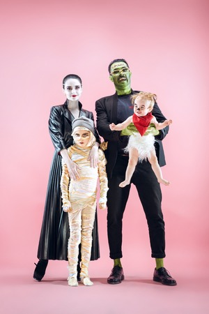 Halloween Family. Happy Father, Mother and Children Girls in Halloween Costume and Makeup. Bloody theme: the crazy maniak faces on pink studio background Stock Photo