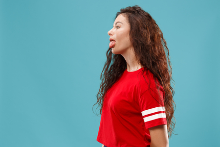 Horrible, stress, shock. Female half-length portrait isolated at blue studio. Young emotional surprised woman clasping head in hands. Human emotions, facial expression concept. Trendy colors. Profile view Stock Photo