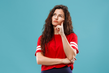 Remember all. Let me think. Doubt concept. Doubtful, thoughtful woman remembering something. Young emotional woman. Human emotions, facial expression concept. Studio. Isolated on trendy blue. Front Stock fotó