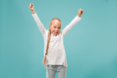 I won. Winning success happy teen girl celebrating being a winner. Dynamic image of caucasian female model on blue studio background. Victory, delight concept. Human facial emotions concept. Trendy colors Stockfoto