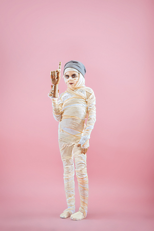 Studio image of a young teen girl bandaged, on pink background. Bloody Halloween theme: the crazy maniak studio background Standard-Bild - 108956608