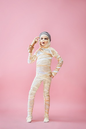 Studio image of a young teen girl bandaged, on pink background. Bloody Halloween theme: the crazy maniak studio background Banco de Imagens - 108956609
