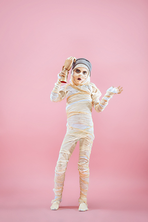 Studio image of a young teen girl bandaged, on pink background. Bloody Halloween theme: the crazy maniak studio background