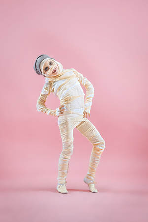 Studio image of a young teen girl bandaged, on pink background. Bloody Halloween theme: the crazy maniak studio background Standard-Bild - 108956619