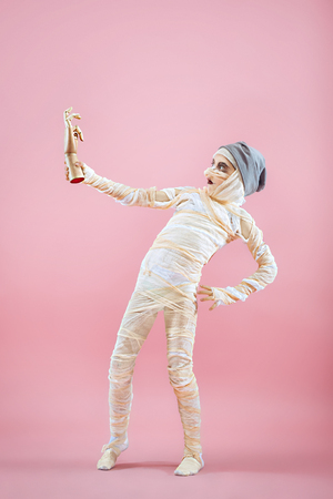 Studio image of a young teen girl bandaged, on pink background. Bloody Halloween theme: the crazy maniak studio background Standard-Bild - 108956620