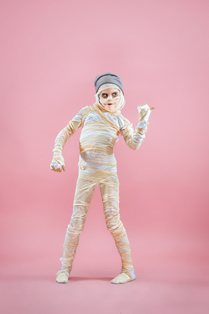 Studio image of a young teen girl bandaged, on pink background. Bloody Halloween theme: the crazy maniak studio background Standard-Bild - 108956627