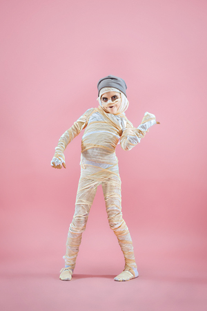 Studio image of a young teen girl bandaged, on pink background. Bloody Halloween theme: the crazy maniak studio background Standard-Bild - 108956628