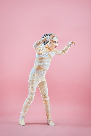 Studio image of a young teen girl bandaged, on pink background. Bloody Halloween theme: the crazy maniak studio background Standard-Bild - 108956629