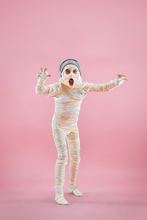 Studio image of a young teen girl bandaged, on pink background. Bloody Halloween theme: the crazy maniak studio background Standard-Bild - 108956630