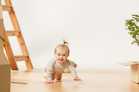Friendly blue eyed baby girl sitting on the floor indoors at home Stok Fotoğraf