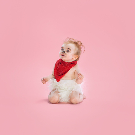 Newborn baby girl wearing a Halloween costume on pink studio background