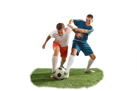 Football players tackling for the ball over white background. Professional football soccer players in motion isolated white studio background. Fit jumping men in action, jump, movement at game.