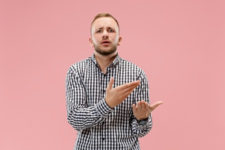 Argue, arguing concept. Beautiful male half-length portrait isolated on pink studio backgroud. Young emotional man looking at camera. Human emotions, facial expression concept