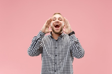 Do not miss. Young casual man shouting. Shout. Crying emotional man screaming on pink studio background. male half-length portrait. Human emotions, facial expression concept. Trendy colors Stok Fotoğraf