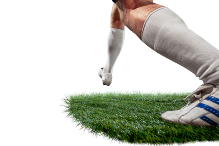 Football playe tackling for the ball over white background. Professional football soccer players in motion on green grass studio background. legs closeup Stock Photo