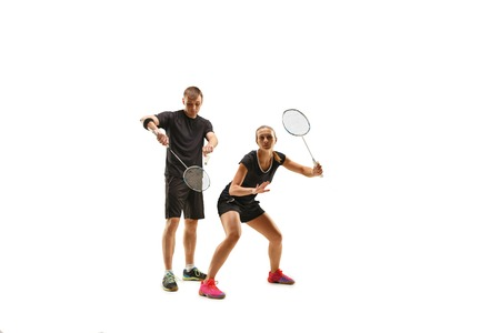 Couple playing with badminton rackets isolated on white studio Stock Photo
