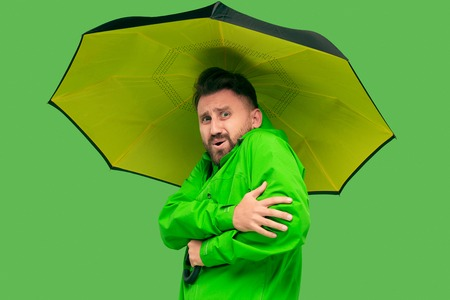 handsome bearded freezing young man holding umbrella and looking at camera isolated on vivid trendy green studio. concept of the onset of autumn and cold