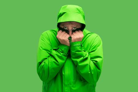 hübscher bärtiger eiskalter junger Mann lokalisiert auf lebhafter trendiger grüner Farbe im Studio. Konzept des Beginns von Herbst und Kälte