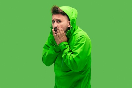 handsome bearded freezing young man isolated on vivid trendy green color at studio. concept of the onset of autumn and cold Stock Photo