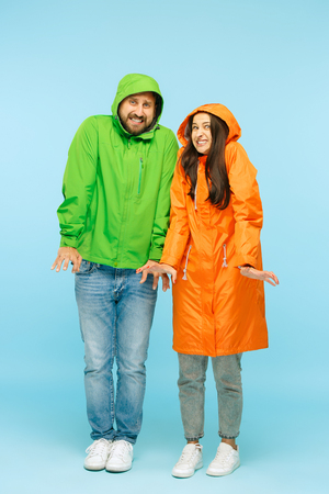 The young couple posing at studio in autumn jacket isolated on blue.