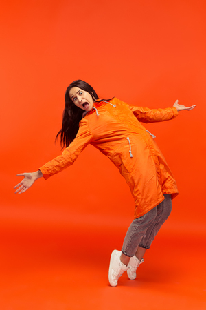 The young girl posing at studio in autumn jacket isolated on red.