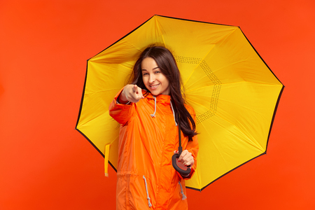 The happy smiling young girl posing at studio in autumn orange jacket and pointing to camera isolated on red.