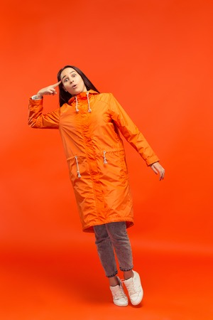 The young girl posing at studio in autumn jacket isolated on red. Human negative emotions.
