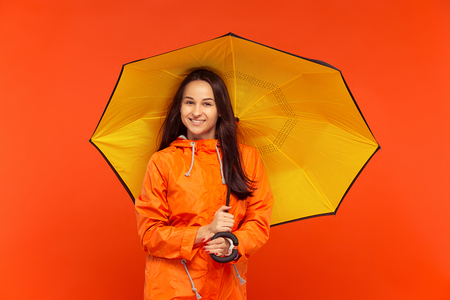 The happy smiling young girl posing at studio in autumn orange jacket isolated on red. Human positive emotions. Banco de Imagens