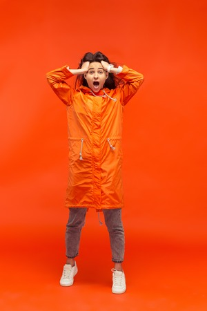 The happy smiling young girl posing at studio in autumn orange jacket isolated on red. Stock Photo