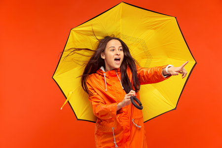 The happy smiling young girl posing at studio in autumn orange jacket and pointing to left isolated on red.