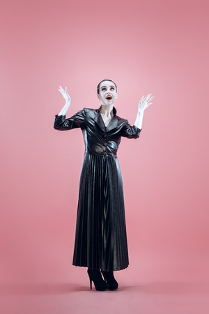 Halloween. Beautiful woman with bright black halloween makeup in a black leather cloak at pink studio 스톡 콘텐츠