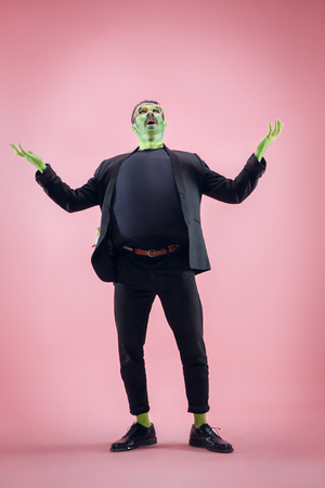 Bloody Halloween theme: The crazy maniak face on pink studio background Stock Photo