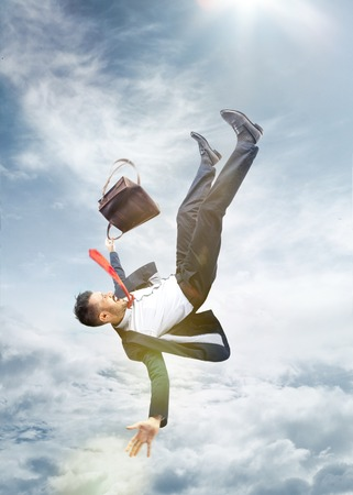 The frightened businessman in suit falling down and screaming against blue sky background. Stock Photo