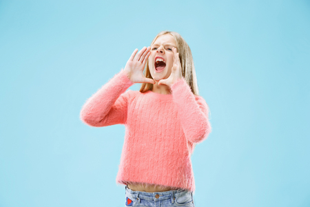 Do not miss. Young casual teen girl shouting. Shout. Crying emotional teenager screaming on blue studio background. Female half-length portrait. Human emotions, facial expression concept. Trendy colors Banco de Imagens