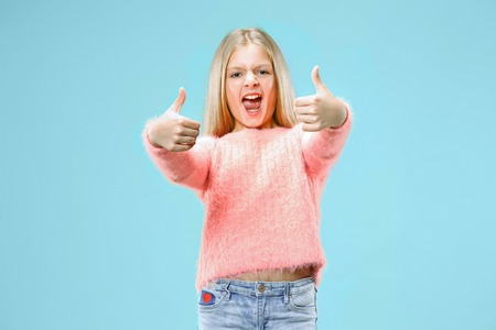 Happy teen girl standing, smiling isolated on trendy blue studio background. Beautiful female portrait. Young satisfy girl with sign ok. Human emotions, facial expression concept. Front view. Stock Photo