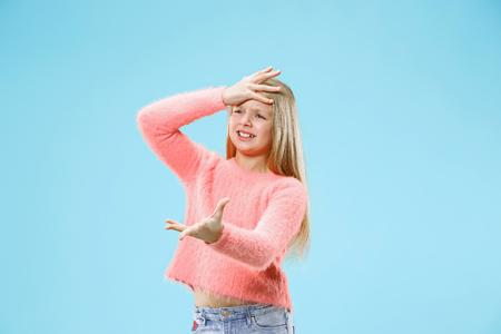 Why is that. Beautiful female half-length portrait on trendy blue studio backgroud. Young emotional surprised, frustrated and bewildered teen girl. Human emotions, facial expression concept.